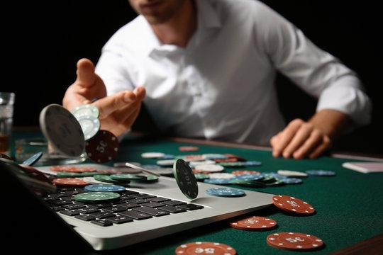 Young man playing poker online, closeup
