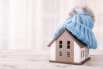 Model of house with hat on table. Winter concept