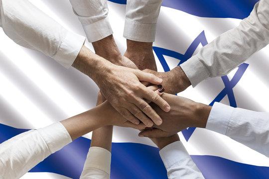 Stack of human hands over waving Israeli flag