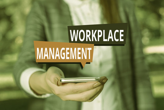 Text sign showing Workplace Management. Business photo showcasing organizing things surrounding you in your working space Woman in grey suites holds mobile phone