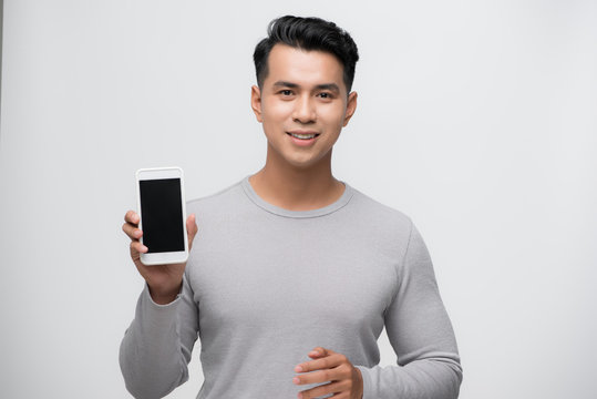 Happy smiling young Asian man showing mobile phone on white