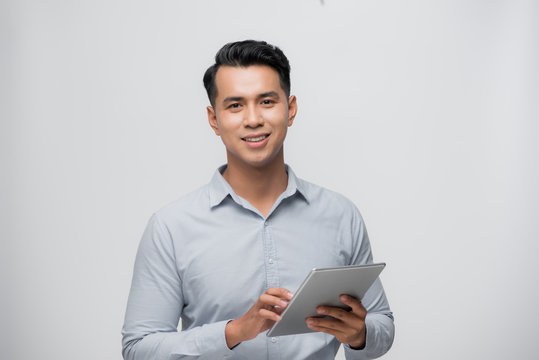 Handsome young Asian man using pad on white background.