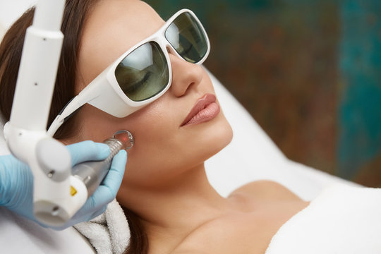 pretty woman receiving face treatment with laser wearing protection glasses
