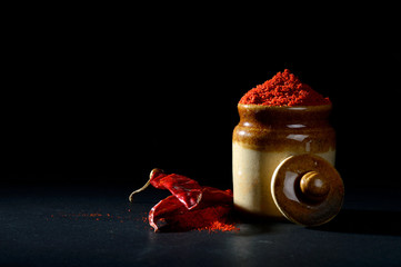 Canvas Prints Hot chili peppers Red Chili Pepper powder in clay pot with Red Chili Peppers on black background