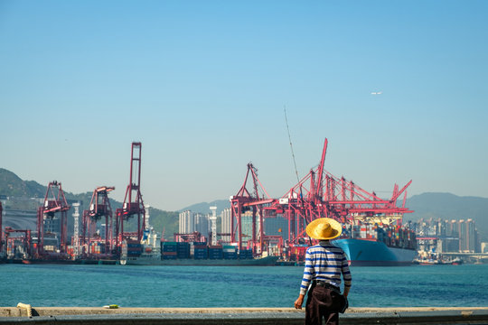 Fisher man with fishing rod from behind near container ship and freight harbour in HongKong