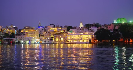 Wall Mural - Lal ghat: Udaipur haveli, houses and ghats on bank of lake Pichola with water riffles. Rajput architecture. Sunset at Udaipur, Rajasthan, India.