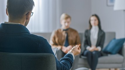 Unfocused Couple on Counseling Session with Psychotherapist. Focus on Back of Therapist Taking Notes and Talking: People Sitting on Analyst Couch, Discussing Psychological and Relationship Problems