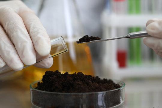 Female chemist in white protective gloves hold test tube