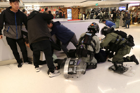 Riot police detain Hong Kong protesters during a Christmas Day rally in Sha Tin shopping mall in Hong Kong