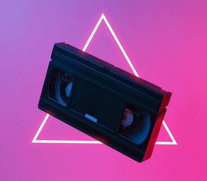 Minimalism retro style concept. 80s. Video cassette in neon red blue light. Retro wave