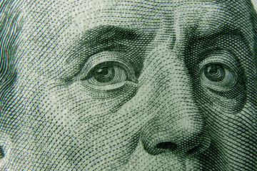 Closeup on Benjamin Franklin eyes from 100 dollar bill. American currency as a world money concept.