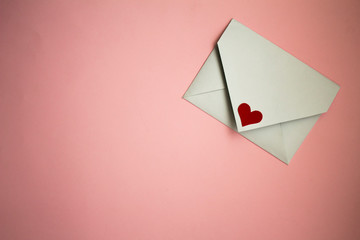 white postal envelope on a pink background, with paper hearts, heart in the form of paper, layout for Valentine's day