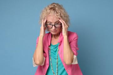 Blonde mature caucasian woman in colored clothes touching her thead feeling stress or ill, on blue background