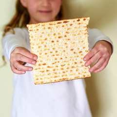 Young Jewish girl holding matzah for Passover.