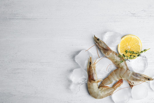 Flat lay composition with raw shrimps on white wooden table. Space for text