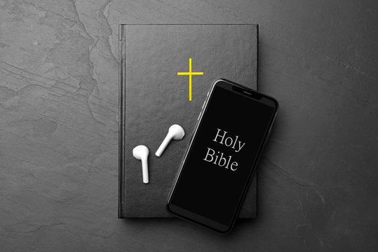 Bible, phone and earphones on black background, top view. Religious audiobook