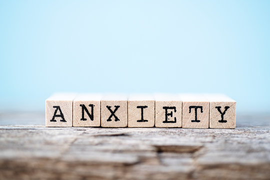 The word anxiety with a wood and light blue background