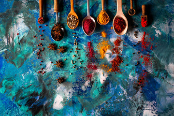Various spices spoons on blue concrete background table. Top view with copy space