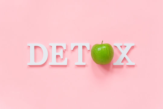 Body detoxification and healthy diet concept. Green natural fresh apple in word DETOX from white letters on pink background. Creative flat lay Top view Copy space