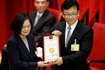 Taiwan President Tsai Ing-wen hand out certification during a graduation ceremony for the Investigation Bureau agents in New Taipei City,