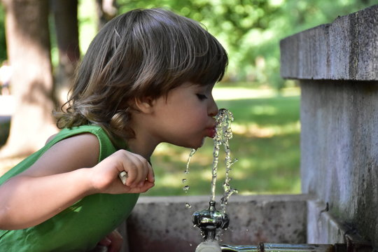 child drinks water from a fountain