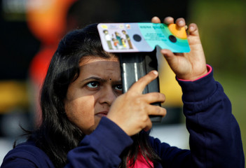 A woman uses her mobile phone and solar viewers to take photographs of the annular solar eclipse in Ahmedabad