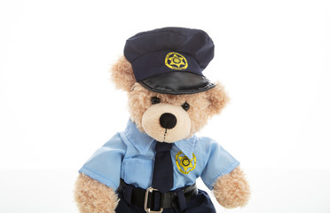 Cute teddy in policeman uniform isolated against white background