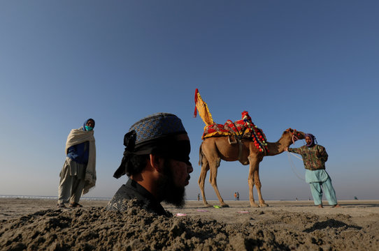 Mehrban Akhtar, 20, blindfolded and buried in sand up to his neck during a solar eclipse, is pictured along Clifton beach in Karachi