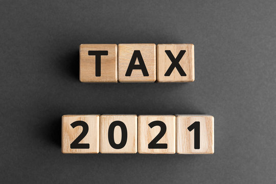 Tax 2021 - phrase from wooden blocks with letters, Tax time 2021 concept, top view gray background