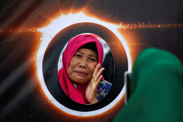 A woman poses for photos behind a banner depicting the solar eclipse during the annular solar eclipse in Siak