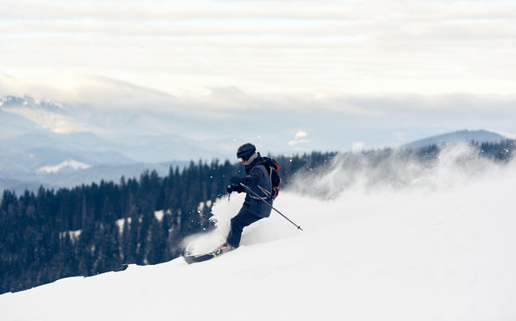 Panoramic photo with skier, winter mountains view. Young man skiing downhill from snow-capped mountain top. Risk, overcoming obstacles, hardiness, victory, achievement concept. Grey sky on background.