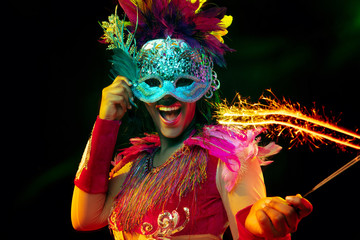 Foto op Plexiglas Carnaval Beautiful young woman in carnival mask and stylish masquerade costume with feathers and sparklers in colorful lights on black background. Christmas, New Year, celebration. Festive time, dance, party.