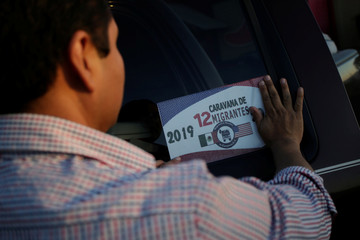 A man places a sticker of the 12th Caravan of Migrants on his car in Laredo, Texas