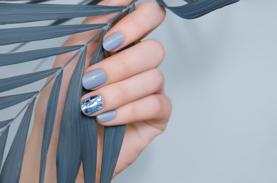 Beautiful female hand with blue nail design