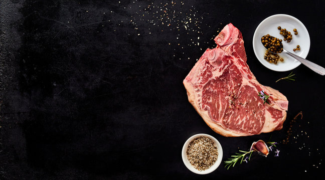 Fresh raw cowboy steak with spice rub and herbs
