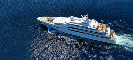 Aerial drone ultra wide photo of luxury mega yacht with wooden deck cruising Aegean deep blue sea