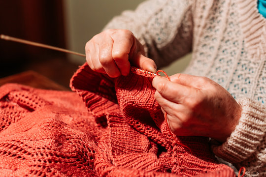 Older woman hands, knitting red sweater. Hobby and leisure