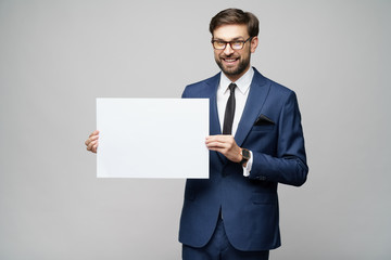 Young businessman holding blank signs over grey background
