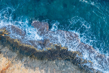Waves beat against a rocky shore, aerial view