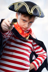 Little boy dressed as a pirate sailor, with an old pistol