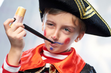 Little boy in a pirate sailor costume smokes a toy pipe.