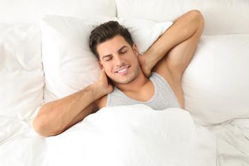 Man awakening in bed at home, top view. Lazy morning Fotomurales