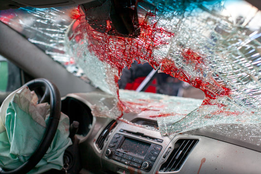 Broken car windshield after an accident with traces of blood and airbag. view from inside