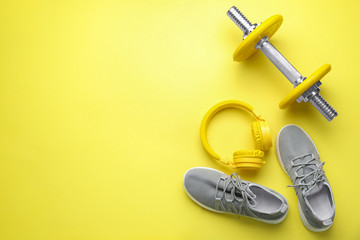 Dumbbell with shoes and headphones on color background