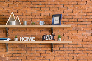 Shelves with decor hanging on brick wall