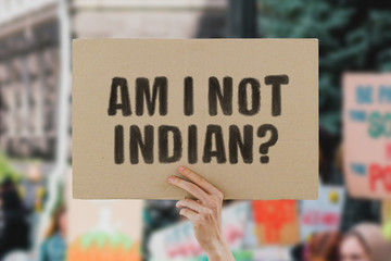 "The phrase "" Am I not indian? "" on a banner in men's hand. Human holds a cardboard with an inscription. CAA. NRC. CAB. NPR. Politics. Discrimination. Delphi. Muslims"