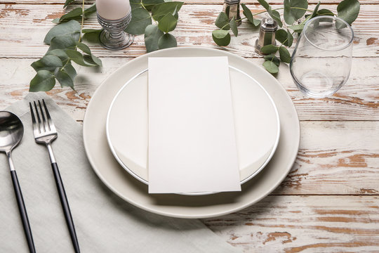 Beautiful table setting with empty menu on white wooden background