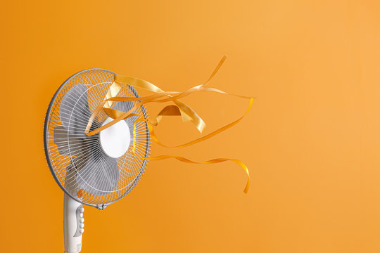 Electric fan with fluttering ribbons on color background