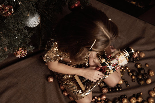 Girl and Nutcracker among golden painted walnuts under the x-mas tree