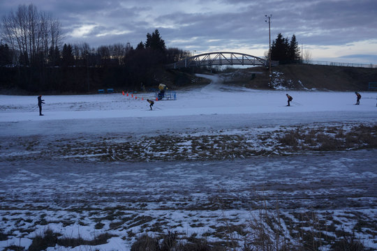 High-school cross-country ski team members practice on a small loop of manmade snow, after winter warmth and rains erased the natural snows at Kincaid Park in Anchorage, Alaska